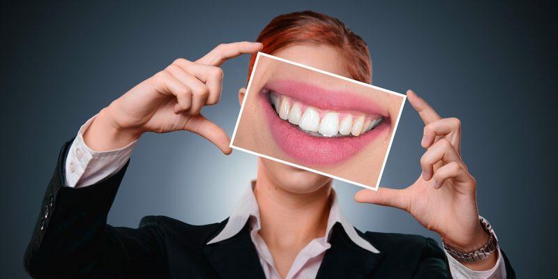 אישה מחזיקה תמונה של שיניים